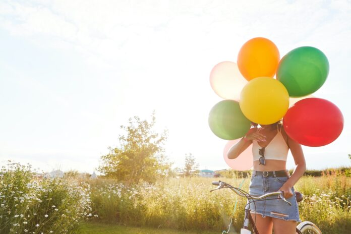 Young Woman With Bicycle Hidden By Balloons Rides Through Countryside Against Flaring Sun